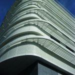 Sun protection fabric and wall cladding follows the curve of the building